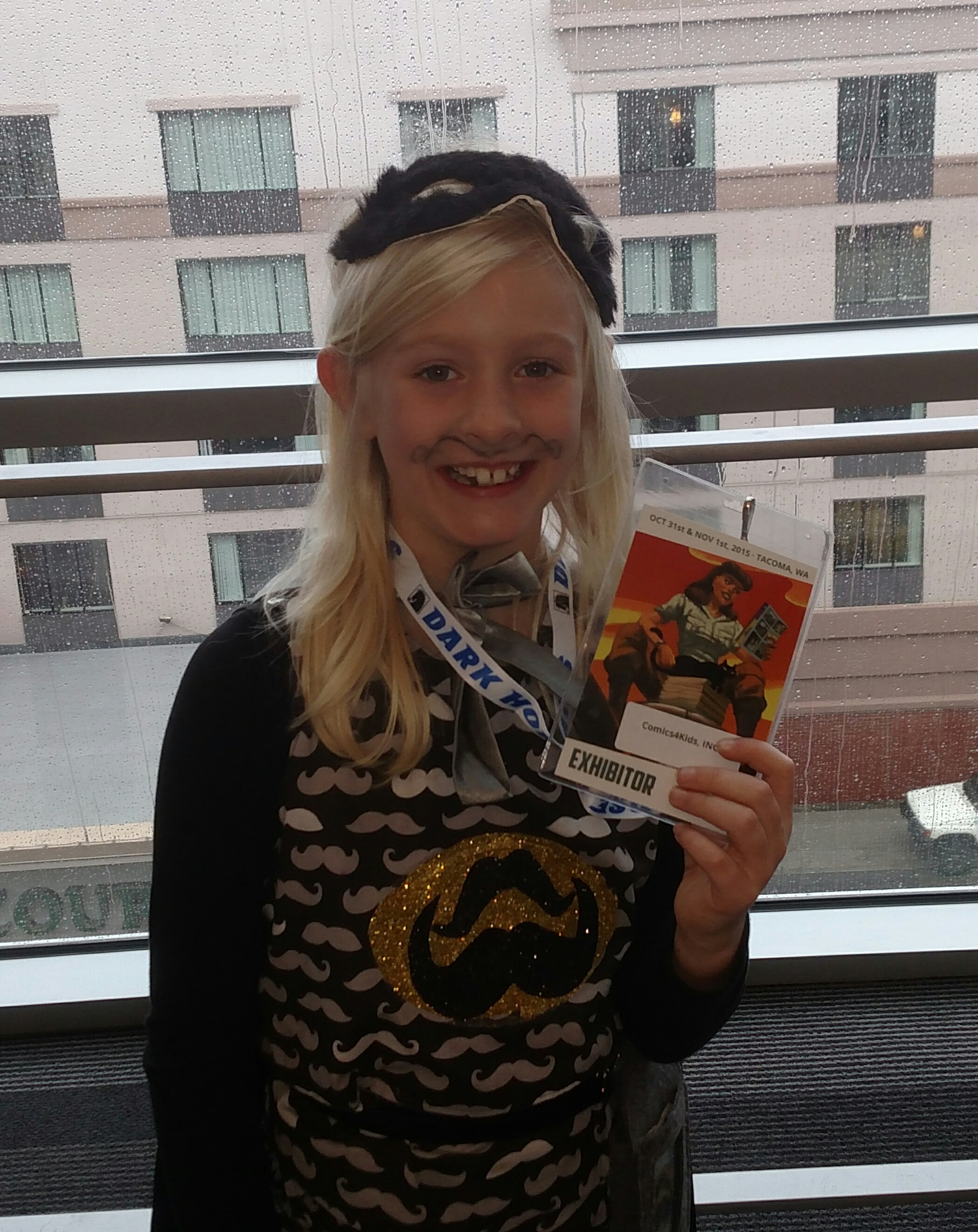 Comics4Kids INC Literacy Champion Lily at her first comic con! with her Comics4Kids INC badge! @ jet city comic show 2015