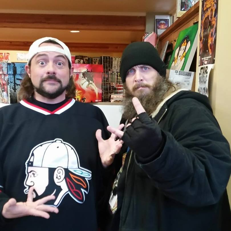 """The 'STASH  is Happy to Help Comics4Kids!"" - Kevin Smith (White Hat) with Comics4Kids INC Vice President Jason McKibbin (Black Hat) 2018"